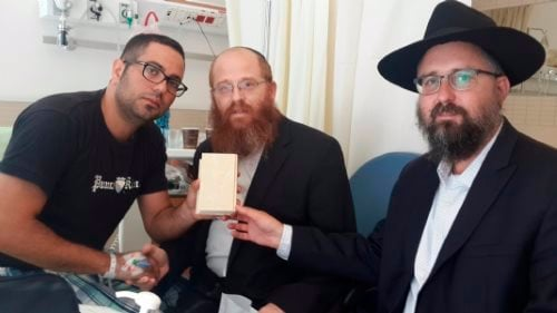 Rabbi Menachem Kutner, right, director of the Chabad Terror Victims Project, and Rabbi Yossi Lipkin of the Chabad House in Kfar Saba, Israel, visit Yair in the hospital and bring him a gift, the book of Chitas.