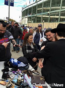 Wrapping tefillin for Jewish passersby.