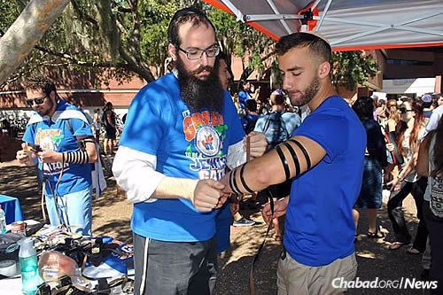 Rabbi Aharon Chaim Notik, co-program director at Lubavitch Chabad Jewish Student Center in Gainesville, helps University of Florida student Ariel Paniry put on tefillin.