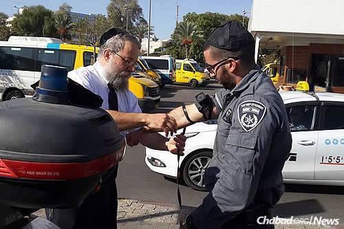 Raichik helps a border policeman in Be'er Sheva don tefillin.