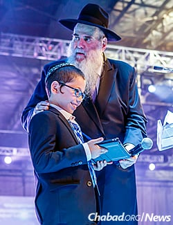 Moshe recited Tehillim (Psalms) in a booming voice to thunderous applause. (Photo: Eliyahu Parypa/Chabad.org)