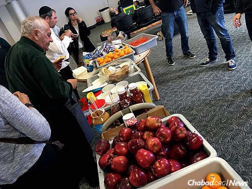 Hundreds of people enjoyed bagels, cold meats, hummus, fresh fruit, chips and more as they lingered in the terminal. (Photo: Hillel Fuld)