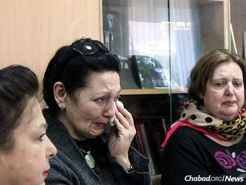 A Jewish refugee from eastern Ukraine reacts emotionally as she tells her story.