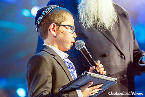 Rabbi Kotlarsky introduced Moshe Holtzberg, the nearly 9-year-old surviving child of Rabbi Gavriel and Rivka Holtzberg, shluchim who were murdered in a November 2008 terror attack on their Chabad House in Mumbai, India. (Photo: Eliyahu Parypa/Chabad.org)