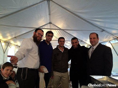 Levi Teichtel, left, and his father, Rabbi Dovid Teichtel—co-director of Illini Chabad with his wife, Goldie—took time for a photo with some of their visitors before Shabbat, including guest speaker Frenkel, far right, and other Israelis.