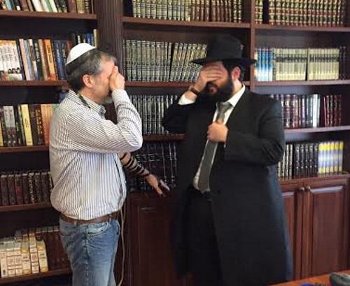 פיטר קונדה מניח תפילין לראשונה בחייו עם הרב שמואל רסקין