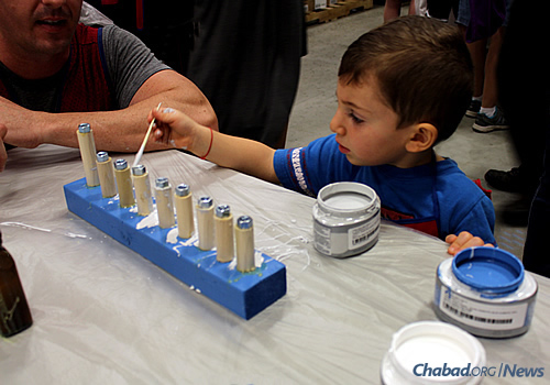 Three-year-old D.J. Becker paints a menorah at a Chanukah workshop sponsored by Chabad at St. Johns County in Florida and Lowe's home-improvement store.