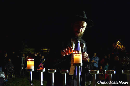 "The recently established Chabad on the Coast, co-directed by Rabbi Eliyahu (""Eli') and Shterna Sara Naiditch, held its very first public menorah-lighting on Sunday at a park overlooking the Tel Aviv promenade and the Mediterranean Sea. Here, the rabbi leads the event, which was attended by nearly 200 people. (Photo: Chabad on the Coast)"
