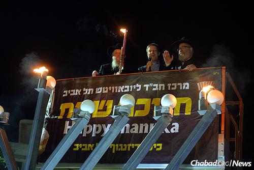 In the cherry-picker, from left: Rabbi Avrohom Shmuel Lewin, director of foreign affairs at Chabad of Tel Aviv; U.S. Embassy spokesman Geoffrey Anisman; and Rabbi Yossi Gerlitzky, head Chabad-Lubavitch emissary in Tel Aviv and director of Merkaz Chabad. ( Photo: Meir Alfasi)