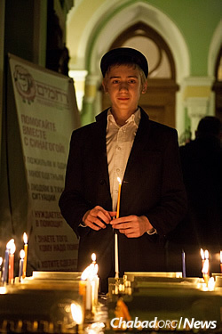 At a Chanukah concert in St. Petersburg, a boy prepares to light his own menorah. More than 500 children attend Chabad's educational system in St. Petersburg, which includes a yeshivah and orphanage.