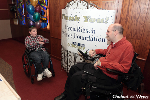 Shmuely Tebbitt, left, with Bryon Riesch, whose charitable foundation provided the boy with a new wheelchair, thanks to the initiative of Shmuley's classmates at Hillel Academy in Milwaukee.