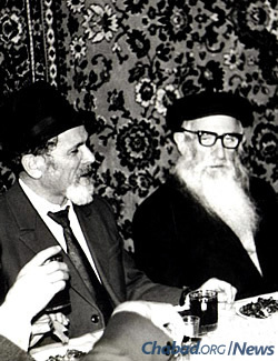 Reb Mottel Lifshitz (left), known as Reb Mottel der Shoichet for his work as a ritual slaughterer, sits next to Reb Getche at a Moscow farbrengen in the 1980s.
