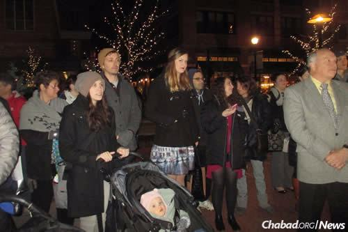 Young families, like those here at this year's public menorah-lighting at Chanukah time, are drawn to the new Jewish programs in town for grownups and kids alike.