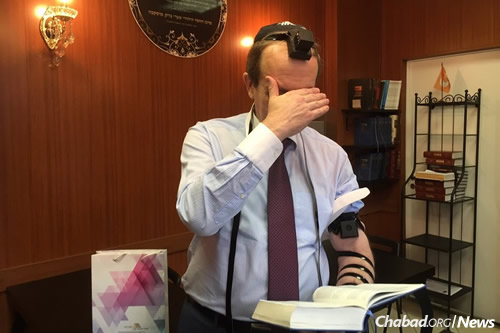 Gov. Alexander Levinthal of Birobidzan wraps tefillin for the first time.