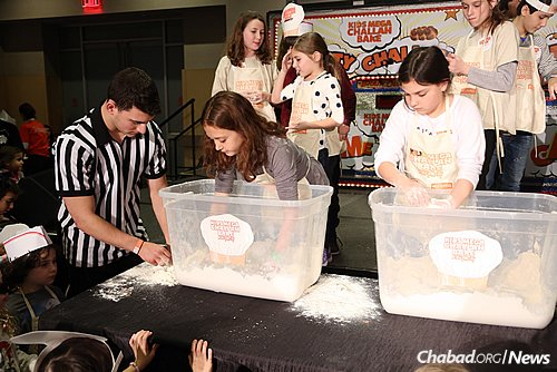 """Children take part in a challah-themed game show during the record-breaking """"Kids Mega Challah Bake"""" in New York City. (Benams Photo)"""