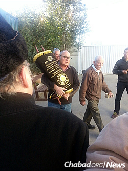 Family members of the fallen soldiers walk in a procession with the completed Torah.