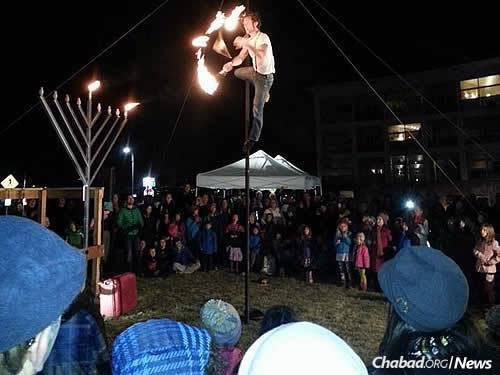 A fire-juggler/acrobat performs for a crowd at Chanukah time.
