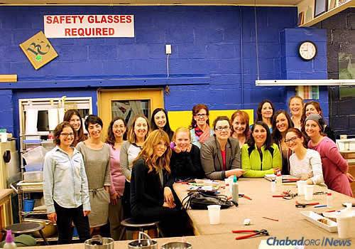 Estee Popack, seated at left of table, organized a Jewish Women's Circle event in a glass studio, where the group made glass mezuzah cases and learned about the significance of a mezuzah.