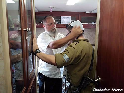 Nachshon helps a soldier don tefillin, a main focus of his work as an emissary of the Rebbe.