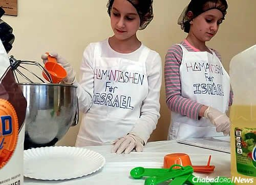 Chaya Mushka and Esther Leah Hodakov, 11-year-old twins from Florida, are baking and selling hamantaschen in the weeks before Purim to raise funds to be sent to terror victims in Israel.