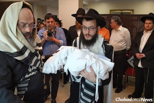 Rabbi Yisroel Kozlovsky holds his newborn son, Gavriel Noach, at the brit milah on Sunday.