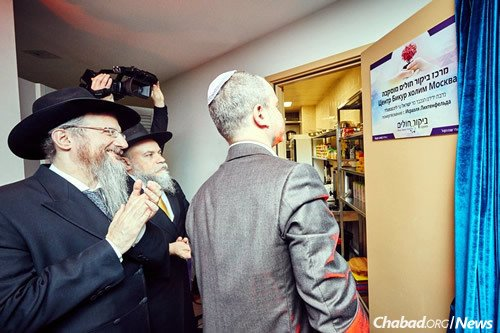 """Rabbis Lazar and Barada look on as a supporter reads the sign on a new commercial kitchen inaugurated at Lazar's daughter's sheva brachot (""""seven blessings"""")."""