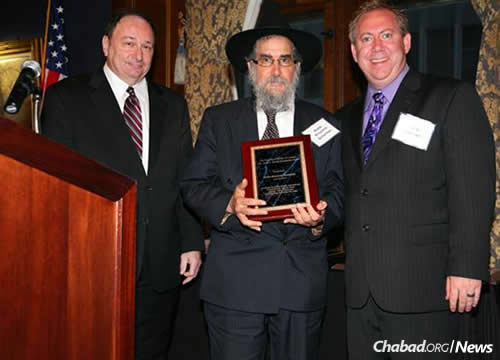 Justice Michael Hyman, left, and attorney James Goldberg present Scheiman with the Gerald Bender Humanitarian Award.