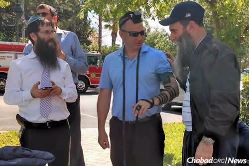 """After learning that the girls were safe, the hotel's manager, Keith Odza, put on tefillin for the first time. He was helped by Rabbi Zvi Konikov, right, of Chabad of the Space & Treasure Coasts. At left is Rabbi Yosef Konikov of Chabad of South Orlando. """"Today is your bar mitzvah,"""" Rabbi Zvi Konikov told Odza. """"We should always remember that when things seem like they can't go right, like this day, darkness can turn into light."""""""
