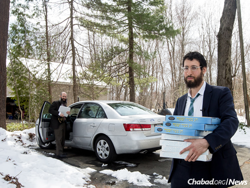 Rabbi Lavy Kosofsky, a Chabad-Lubavitch emissary in Longmeadow, holds boxes of shmurah matzah in Hatfield, Mass. His father, Rabbi Noach Kosofsky, principal of the Lubavitcher Yeshiva Academy in Longmeadow, stands by the car. (Photo: Pearl Gabel)