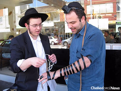 Taking time to wrap tefillin with Jewish men and boys over the age of 13