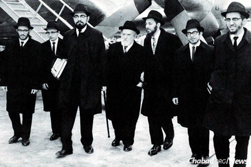 The first shluchim (Avrohom Altein, Leibel Kaplan, Hirshel Lipskier, Shloma Majeski, Yosef Minkowitz and Hirshel Morozov) with Rabbi Eliyahu (Yaichel) Simpson, center, arriving at the airport in Australia.
