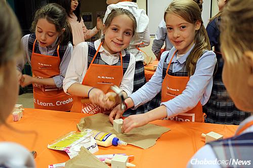 Kids make Chanukah dreidels from wood at a local Home Depot holiday workshop.