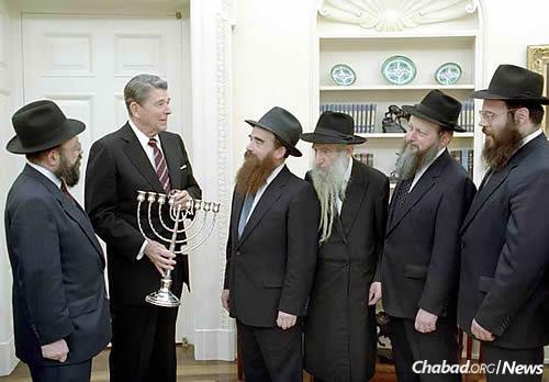 With President Ronald Reagan in the White House at Chanukah time are, from left: Rabbi Moshe Feller, Rabbi Avraham Shemtov, Rabbi Shmuel Dovid Raichik, Rabbi Moshe Herson and Rabbi Yossi Groner.