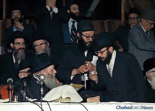 """The rabbi approaches the Rebbe for a private word and a """"l'chaim"""" during a farbrengen in the 1970s."""