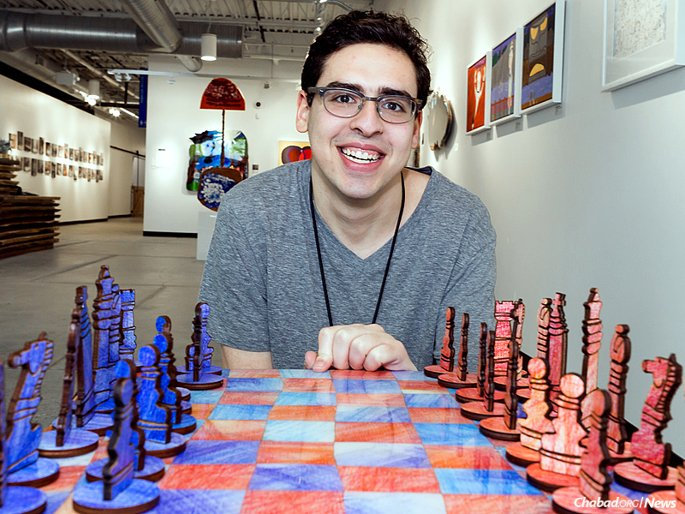 Artist David Kole sits in the Soul Center's Rissman Gallery in front of the chess set he designed and made. (Photo: Brandon Schwartz)