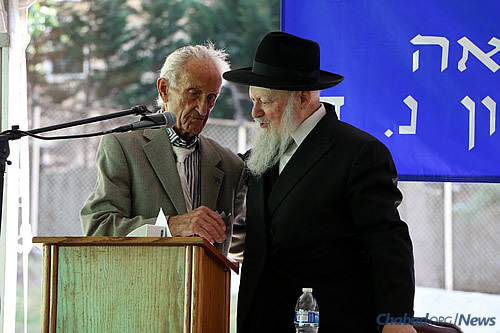 Dean of the college Rabbi Moshe Herson, director of Lubavitch of New Jersey, congratulates Ed Mosberg of Parsippany, N.J., a college trustee who presented the Torah scroll.