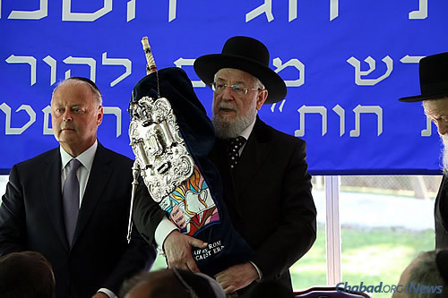 Rabbi Israel Lau, former Ashkenazi chief rabbi of Israel and current chief rabbi of Tel Aviv. holds a 200-year-old Torah scroll rescued from the Holocaust. He is flanked by Miles Berger, a trustee of the college.
