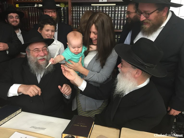 """Rivky Berman's youngest nephew, Zalman Backman, gets ready to write a letter in """"Rivky's Torah,"""" assisted by Rabbi Yisrael Deren, seated at left, and the scribe, Rabbi Moshe Klein, at right."""