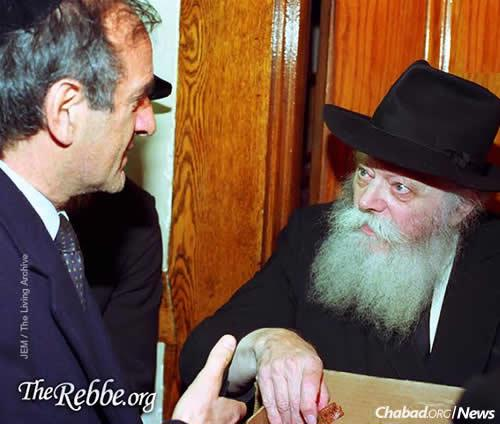 Wiesel receives honey cake from the Rebbe prior to the Jewish holiday of Rosh Hashanah. (Photo: JEM/The Living Archive)
