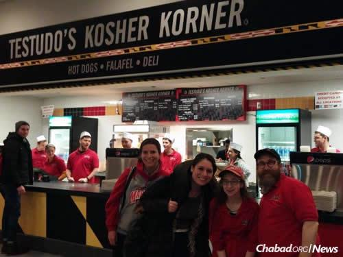 Alumni Tamar May and Rachel Rosner return to the University of Maryland for a game and to visit Rabbi Eli Backman, co-director of the Bais Menachem Chabad Jewish Student Center, at the kosher food stand with his daughter, Chaiky.