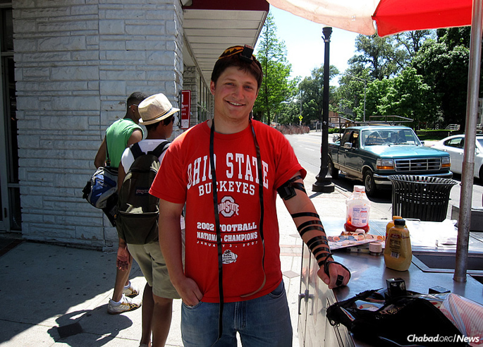 Dan Heldman dons tefillin near the well-known and long-established kosher hot-dog cart at Ohio State University in Columbus, initiated by Rabbi Zalman and Sarah Deitsch of the Schottenstein Chabad House at OSU, soon after the couple arrived on campus.