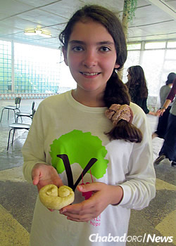 Showing off a homemade creation last year at the first Gan Israel Yeka camp for girls.