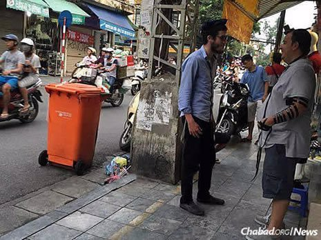The duo spent significant time searching Hanoi's teeming markets for Jewish people. Here, Dubinsky talks with another Jewish man.