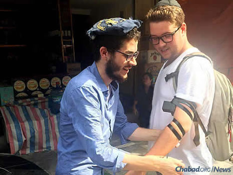 """The word """"Shalom!"""" called out from a rickshaw alerted Dubinsky, left, that there was a Jewish person inside, who got out and put on tefillin."""