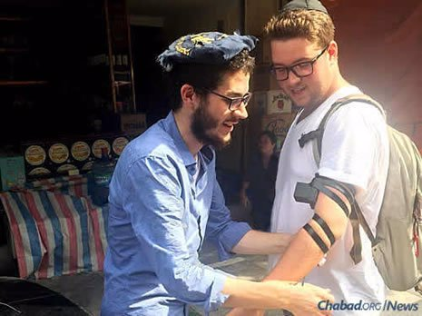 "The word ""Shalom!"" called out from a rickshaw alerted Dubinsky, left, that there was a Jewish person inside, who got out and put on tefillin."