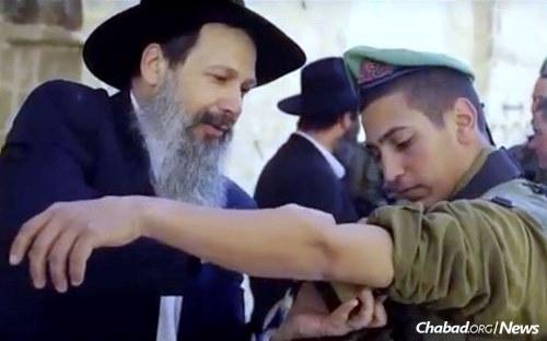 Rabbi Viktor Atia puts tefillin on an Israeli soldier.