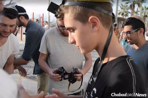 Wrapping tefillin on the streets of Tel Aviv.
