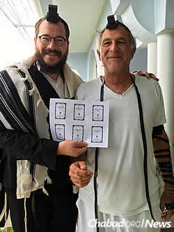 Rabbi Yaakov Raskin, left, with the unbound pages of a new Tanya in Port Antonio.