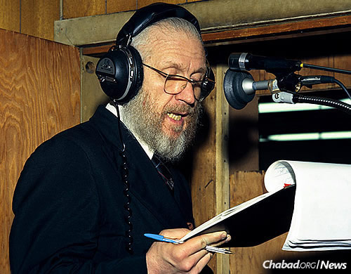 Rabbi JJ Hecht reads from his notes during a live running English translation of the Rebbe's Yiddish talks at a farbrengen. The translation, later joined by others in Hebrew, French and Russian, was broadcast over shortwave radio. (Photo: JEM/The Living Archive)