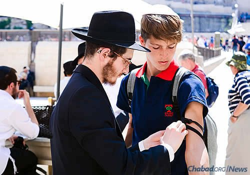 During the long summer days, as many as 1,000 Jewish men and boys over the age of 13 put on tefillin. (Photo: Chabad of the Western Wall)